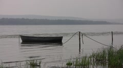 Old lonely pair-oar boat swaying on the river waves in a sunny early morning aga Stock Footage