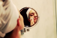 Beautiful young woman with a mirror and cotton pads in the bathroom Stock Footage