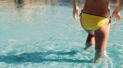 Rear view of woman in yellow bikini standing in the pool Stock Footage