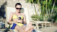 Stock Video Footage of Young woman lying on sunbed and sending sms from a cellphone