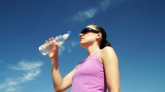 Young woman drinking water against the blue sky Stock Footage