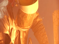 Pan From Guys Mask To Molten Metal Being Poured copy Stock Footage