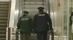 Policmen going up on escalator Stock Footage