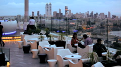 People enjoying a relaxed drink in a rooftop bar in Mumbai, India Stock Footage