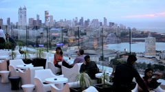 Great view from a rooftop bar where people are relaxing, Mumbai, India - stock footage