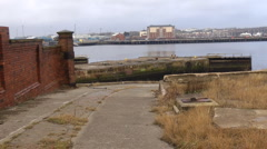 Slipway of old ship yard with modern development across the river - stock footage