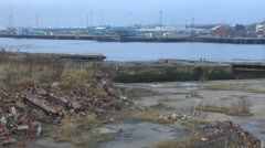 Derelict old ship yard littered with red bricks river in background Stock Footage