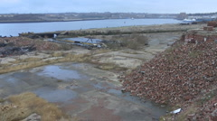 Remains of old ship yard, long out of use, with piles of red brick - stock footage