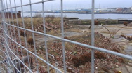 Stock Video Footage of Old deserted ship yard through wire fence