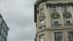 Pan from elegant old historic stone building to more modern office block. Stock Footage
