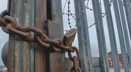 Stock Video Footage of Locked and chained heavy metal gate with razor wire on top.
