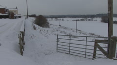 Snow covered fields though an open farm gate. Stock Footage