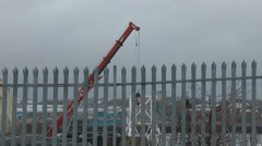 Small crane lifting metal in ship yard, seen through metal fence. Stock Footage