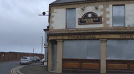 Stock Video Footage of Boarded up public house outside gates of old ship yard,