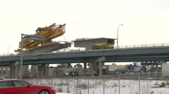 West LRT Construction, elevated guideway crane, low angle with freight train   Stock Footage