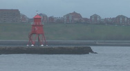 Red painted lighthouse on breakwater in river mouth, choppy waves lap at rocks Stock Footage