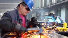 Workers grinding and welding in a factory - stock footage