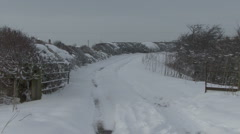 Slow zoom out along a snowy country lane. Stock Footage