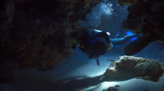 Scuba divers swimming through a cave Stock Footage