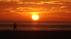 Couple walks by at sunset on the beach Stock Footage
