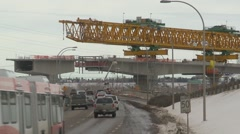 West LRT Construction, elevated guideway crane passing over traffic Stock Footage