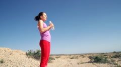 Young woman drinking water in desert environment Stock Footage