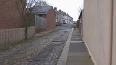 Cobbled urban alley  Road sweeper turns corner then leaves street at next corner Stock Footage