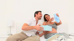 Pretty couple opening gifts Stock Footage