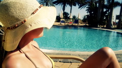 Woman in summer hat sunbathing by the pool Stock Footage