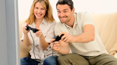 Cute couple playing a video game with with two joysticks Stock Footage