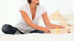 Relaxed woman opening a gift - stock footage