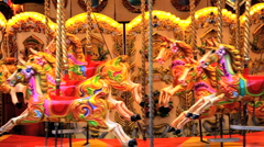 Carousel moving with colourful wooden horses, London England Stock Footage