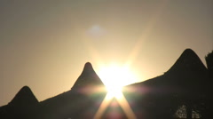 Aurinko laskee takana rannalla aurinkovarjot 01 Arkistovideo