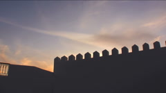 Sun sets behind castle wall in Egypt Stock Footage