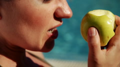 Closeup of female mouth biting apple with swimming pool in the background Stock Footage