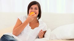 Cute brown-haired lady smelling an orange Stock Footage