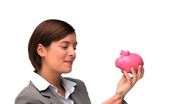 Brown-haired woman saving up money in a piggy bank Stock Footage