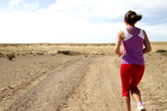 Young woman jogging on desert track, slow motion, shot at 60fps Stock Footage