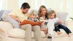 Cute family looking at some albums in the living room Stock Footage