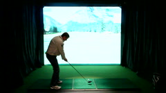 Man practicing swing with an indoor golf simulator Stock Footage