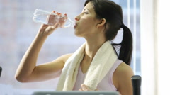 Young woman drinking water after exercising Stock Footage