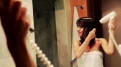 Young woman drying her hair in front of the mirror Stock Footage