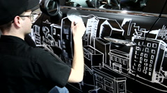An artist drawing on the surface of a grey mini cooper Stock Footage