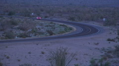 Stock Video Footage of Cars Around Curve On Dusky Desert Highway