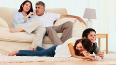 Family laughing in front of tv Stock Footage