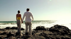 Young couple standing on the seashore, back view Stock Footage