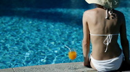Woman in hat relaxing beside the pool Stock Footage