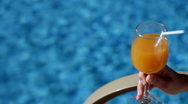 Woman drinking cocktail by a swimming pool  Stock Footage