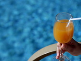 Woman with cocktail by a swimming pool  Stock Footage