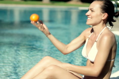 Portrait of happy woman with orange fruit outdoors, slow motion Stock Footage